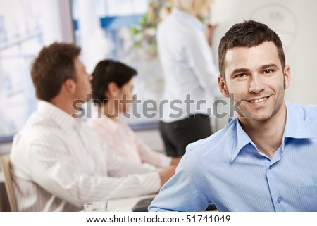 Happy young businessman in business meeting at office, looking at camera smiling. - stock photo
