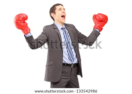 Happy young businessman in suit with red boxing gloves gesturing happiness isolated on white background - stock photo