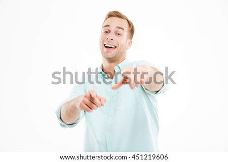 Happy young businessman laughing and pointing on you over white background - stock photo