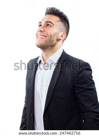 Happy young businessman looking up