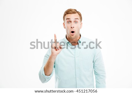 Happy young businessman pointing up and having an idea over white background