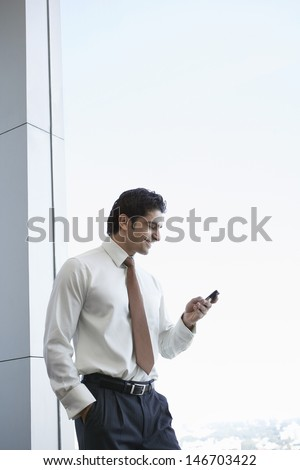 Happy young businessman reading text message on cell phone - stock photo