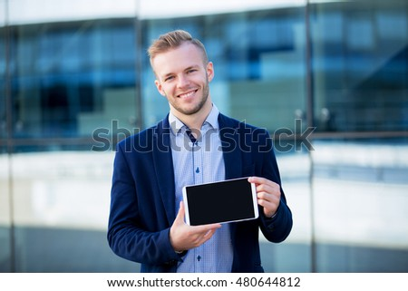 Happy young businessman showing a tablet on a background of blue glass building