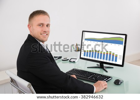 Happy Young Businessman Sitting In Office With Graph On Computer