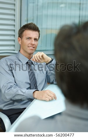 Happy young businessman sitting outdoor on office terrace and talking, smiling. Over the shoulder view. - stock photo