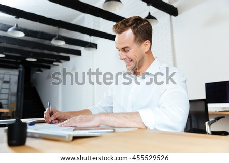 Happy young businessman smiling and writing at the table - stock photo