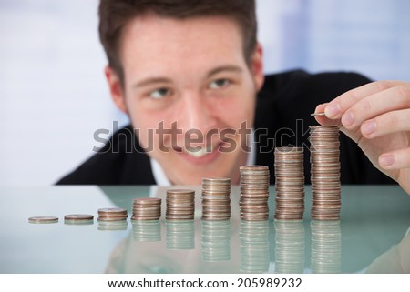 Happy young businessman stacking coins in increasing order at office desk - stock photo