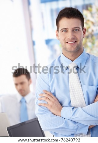 Happy young businessman standing arms crossed in office, smiling.?
