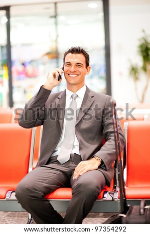 happy young businessman talking on mobile phone at airport