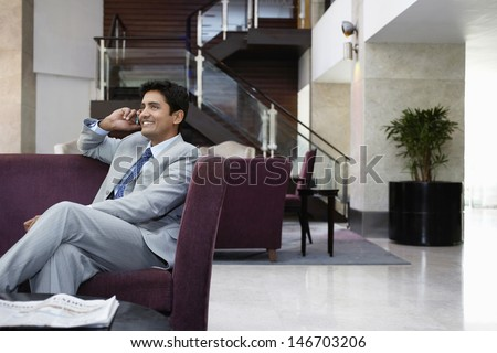 Happy young businessman using cell phone in hotel lobby - stock photo