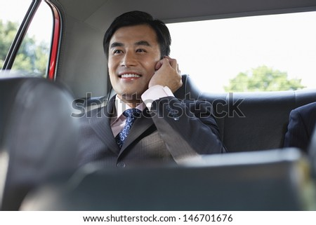 Happy young businessman using cellphone in backseat of car - stock photo