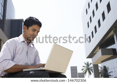 Happy young businessman using laptop outside office building - stock photo
