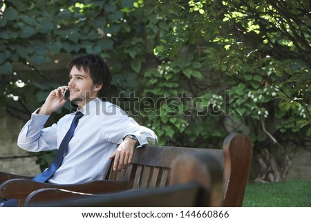 Happy young businessman using mobile phone on park bench - stock photo