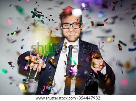Happy young businessman with bottle of champagne and two flutes