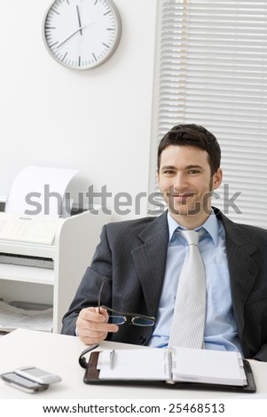 Happy young businessman working at desk at office, smiling.