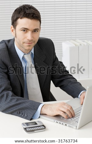Happy young businessman working on laptop computer at office, smiling.