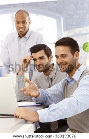 Happy young businessmen working together in office, using laptop computer.