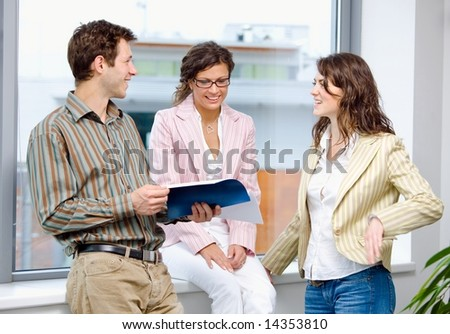 Happy young businesspeople having meeting at office and reading documents, smiling.