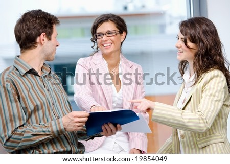 Happy young businesspeople having meeting at office and reading documents, smiling. - stock photo