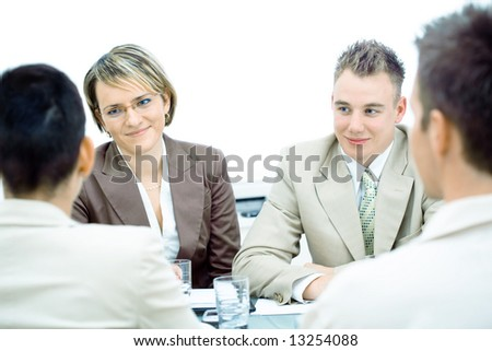 Happy young businesspeople talking on meeting at office. - stock photo