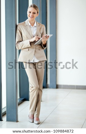 happy young businesswoman full length portrait with a tablet computer - stock photo