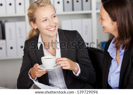 Happy young businesswoman having coffee while looking at coworker in office - stock photo