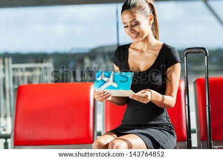 happy young businesswoman looking at her air ticket - stock photo