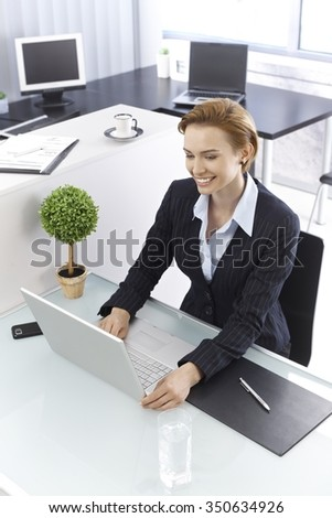Happy young businesswoman sitting at desk, working with laptop computer. Photographed from above. - stock photo