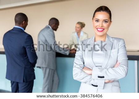 happy young businesswoman standing at hotel reception - stock photo