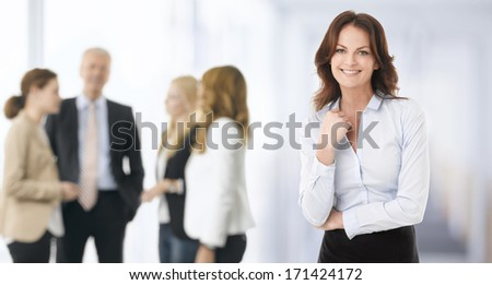 Happy Young Businesswoman Standing In Her Office. Her colleagues in the background.