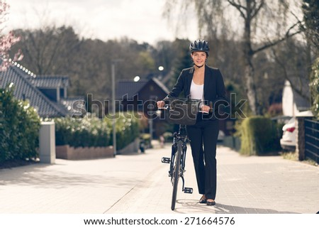 Happy Young Businesswoman standing on the Street with her bike ready to go to the office, Looking at the Camera - stock photo