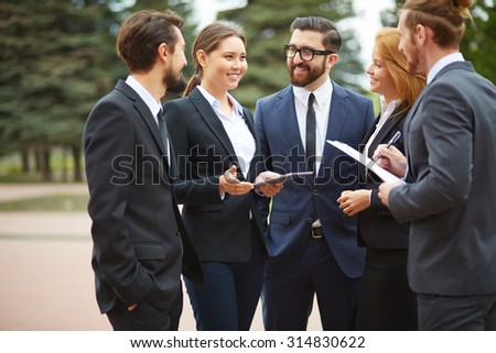Happy young businesswoman talking to colleagues at meeting - stock photo