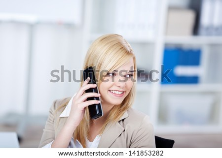 Happy young businesswoman using cordless phone while looking away in office - stock photo