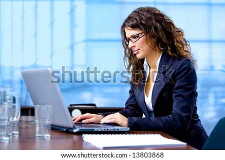 Happy young businesswoman working on laptop computer at office, smiling. - stock photo
