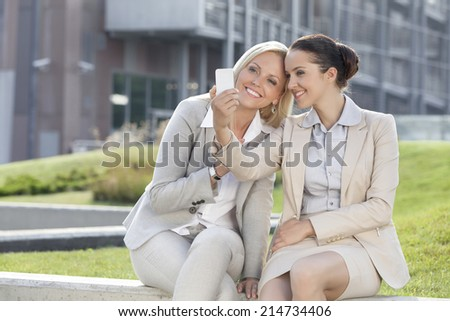 Happy young businesswomen taking self portrait through mobile phone against office building - stock photo