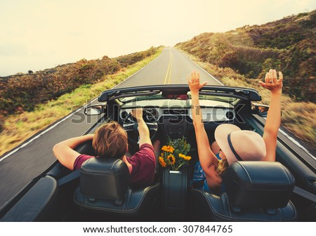 Happy Young Carefree Couple Driving Along Country Road in Convertible at Sunset