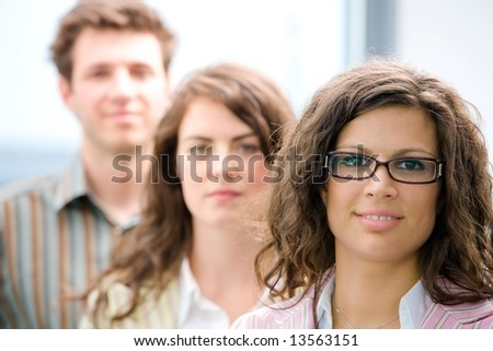 Happy young casual business people standing in a row, smiling. - stock photo