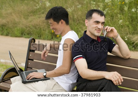 Happy young casual men outdoor with laptop and phone - stock photo