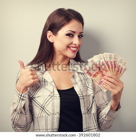 Happy young casual woman in glasses holding roubles and showing thumb up sign with toothy smiling. Toned portrait - stock photo