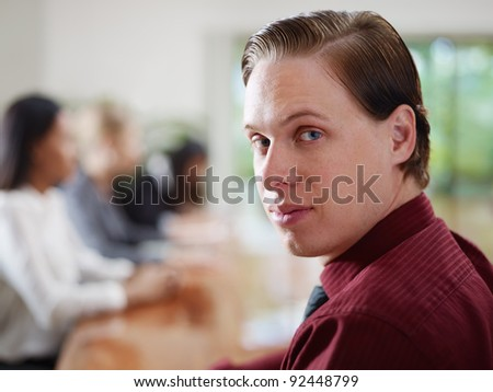Happy young caucasian businessman smiling at camera during business meeting with colleagues. Rack focus - stock photo