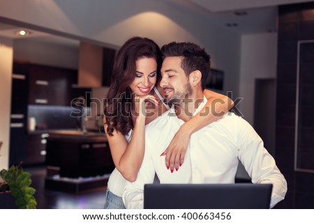 Happy young caucasian couple at home, woman embrace man at laptop  - stock photo