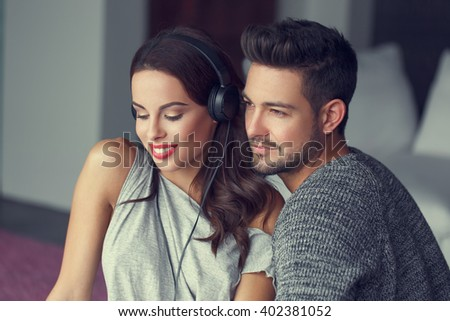 Happy young caucasian couple listening music at home