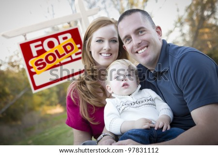 Happy Young Caucasian Family in Front of Sold Real Estate Sign. - stock photo