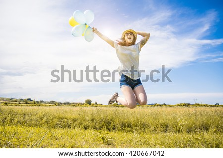 Happy young caucasian girl is jumping holding colored balloons in the air - Portrait of an attractive woman expressing her freedom - stock photo