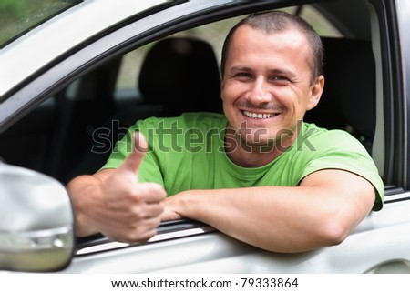 Happy young caucasian man at the wheel of his new car
