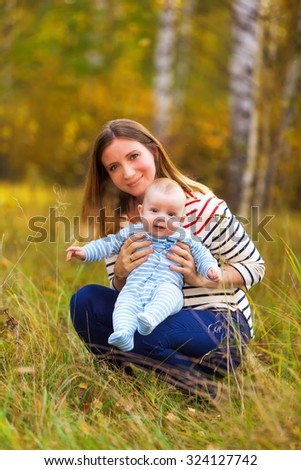 Happy Young Caucasian mother and son outdoors in park on sunny autumn day.  - stock photo