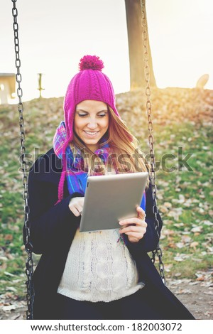 Happy young Caucasian pregnant woman with tablet computer outdoors sitting on swing in park on a sunny winter day. Mother expecting a baby using digital tablet enjoying outdoor. - stock photo
