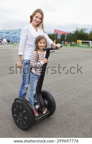 Happy young caucasian woman and her daughter on the segway in the city  - stock photo
