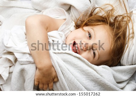 Happy young child rolling in white covers - stock photo