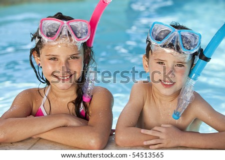 Happy young children, boy and girl, relaxing on the side of a swimming pool wearing blue and pink goggles and snorkel - stock photo